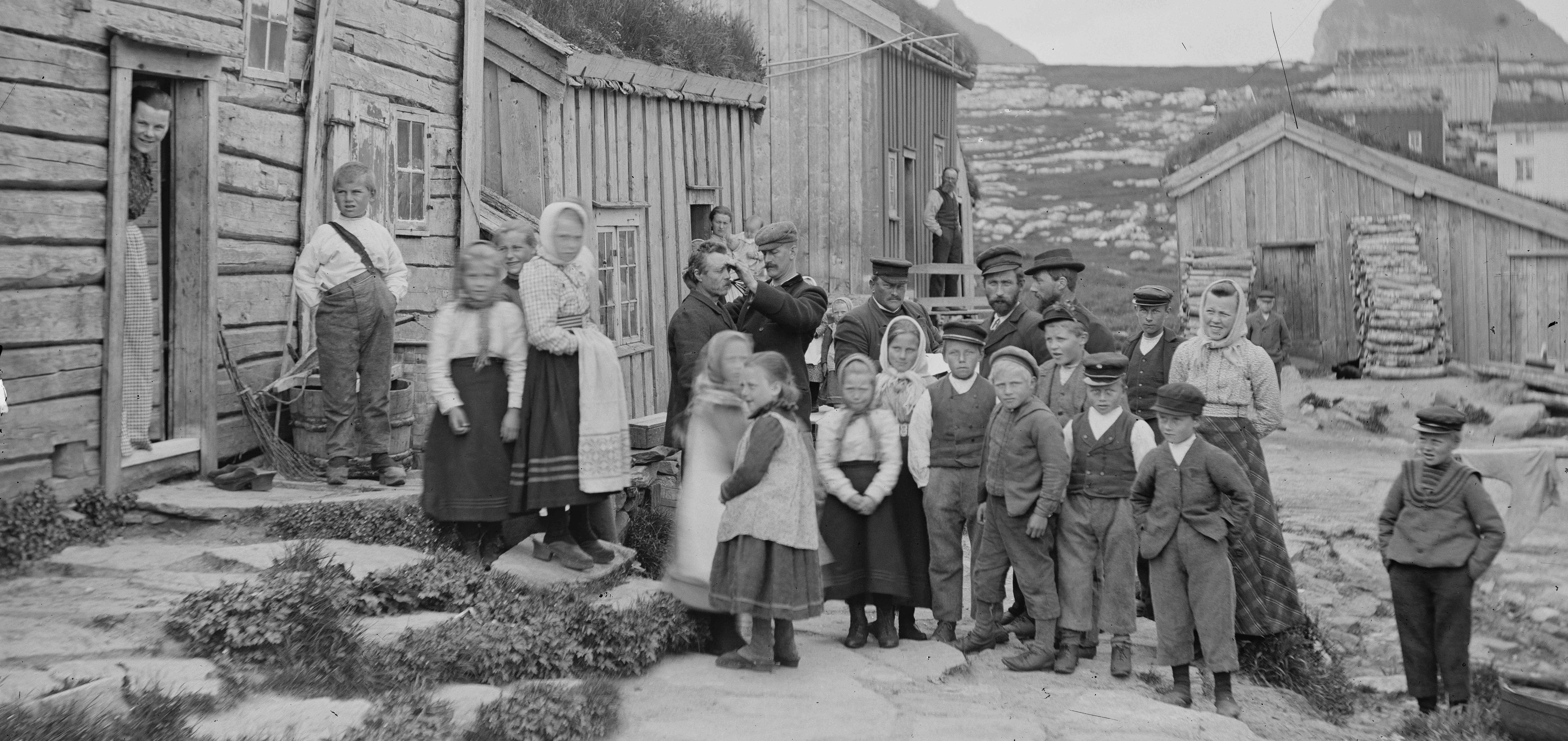 Barn og voksne foran eldre hus. Foto.