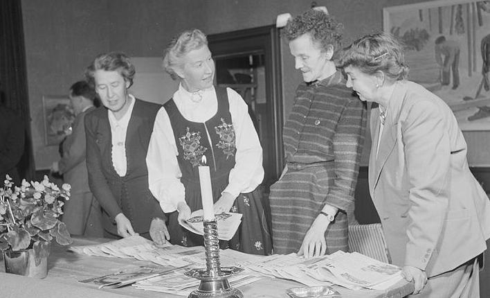 Fire kvinner står ved bord, snakker sammen og ser på ting på bordet