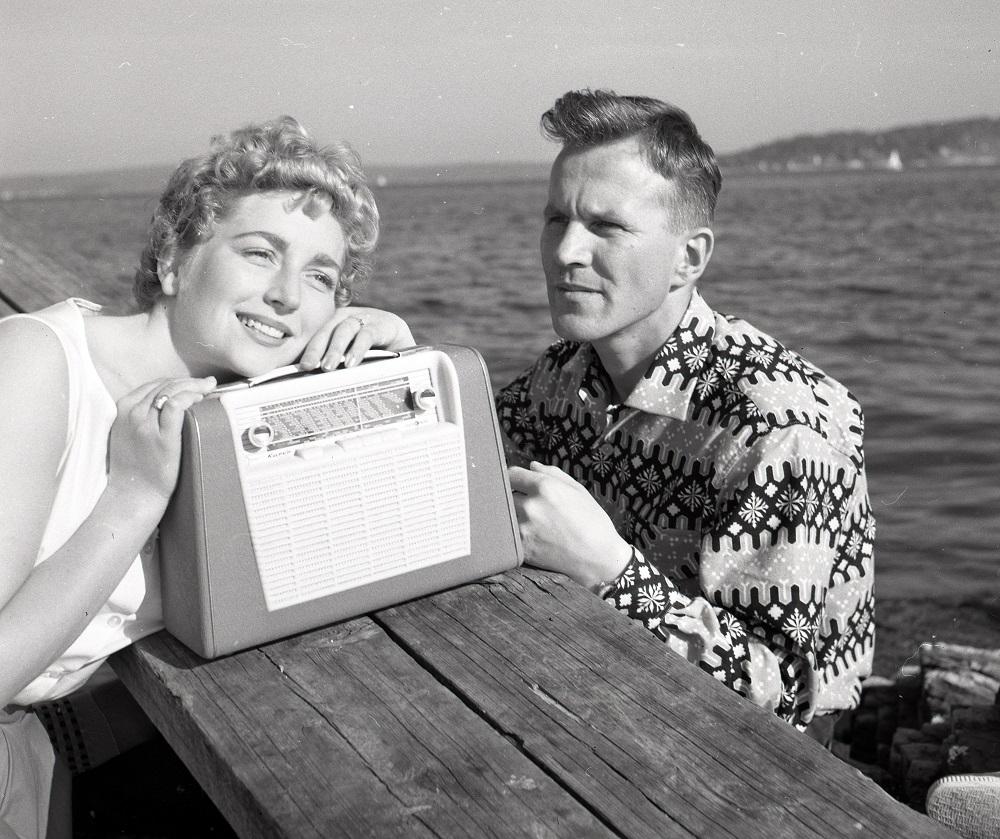 Bilde av 2 personer som sitter og lytter til radioen.