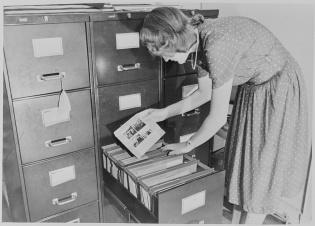 En dame som leter i en arkivskuffe