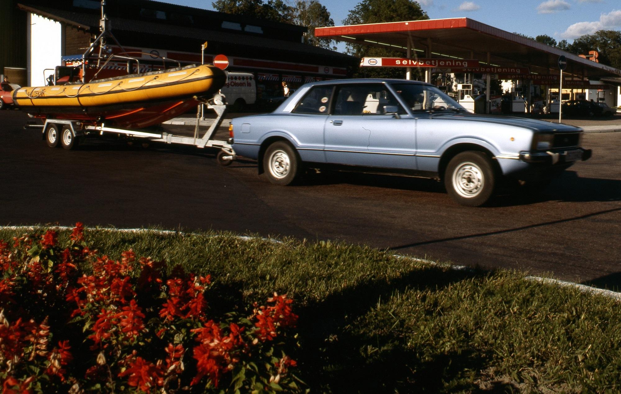 Blå bil utenfor en bensinstasjon