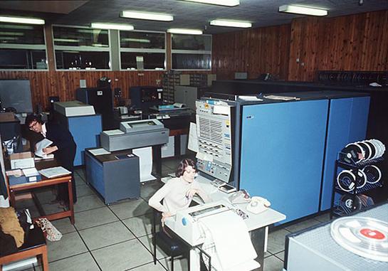Bilde fra datarom med store datamaskiner og to personar.