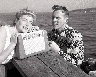 Kvinne og mann lytter til reiseradio av typen Radionette, 1963 eller litt seinere.
