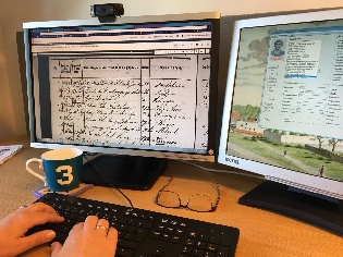 Hender som skriver på tastatur foran to skjermer. Foto.