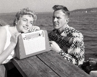 "A couple listen to a ""Radionette"" travel radio ca. 1963."