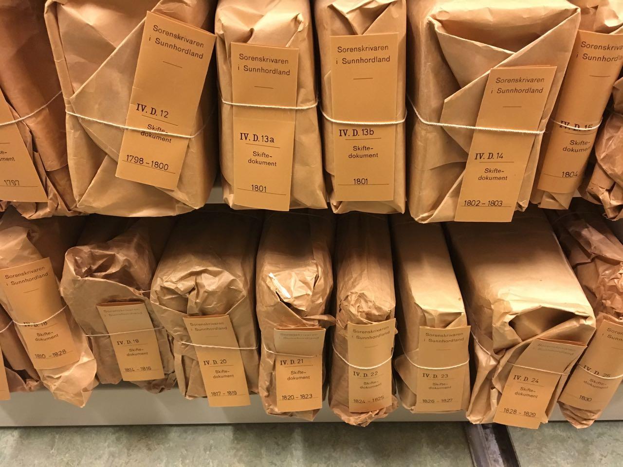 Foto av innpakkede skiftedokumenter på hylle i arkivmagasin
