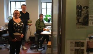 Tre personer titter ut av kontoret.
