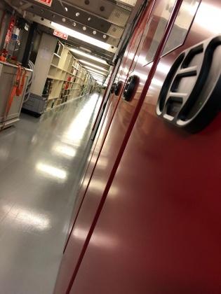 Viser korridor med rullemagasin til høyre. Foto.